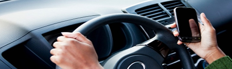Driver distraction example. Image of woman holding phone while steering a car.