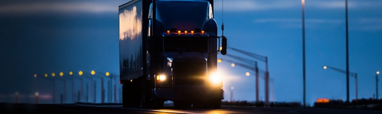 Image of a truck driving at nighttime - a prime scenario for driver drowsiness.