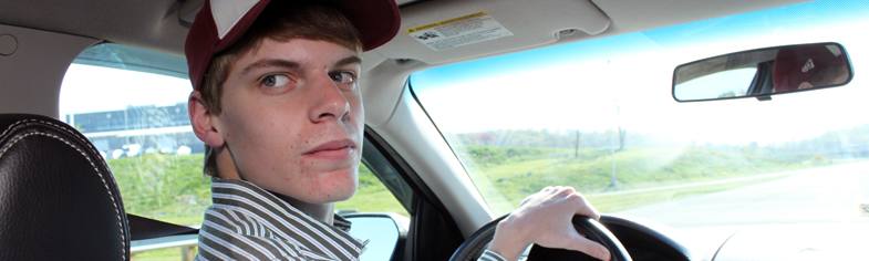Teaching teens best practices for sharing the road. Image of male teen driver checking blind spots.